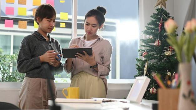 Zwei junge designerfrauen, die ihren partnern im konferenzraum einige neue ideen zum projekt auf dem digitalen tablet geben.