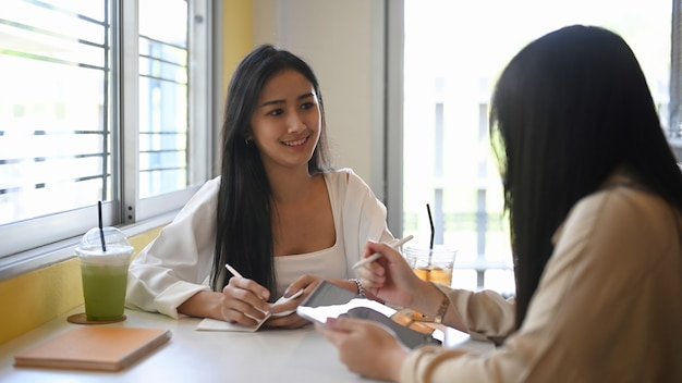 Zwei junge designerinnen, die über neues projekt sprechen, während sie zusammen im café sitzen.