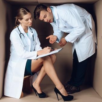 Zwei junge doktoren in den weißen mänteln in der pappschachtel.
