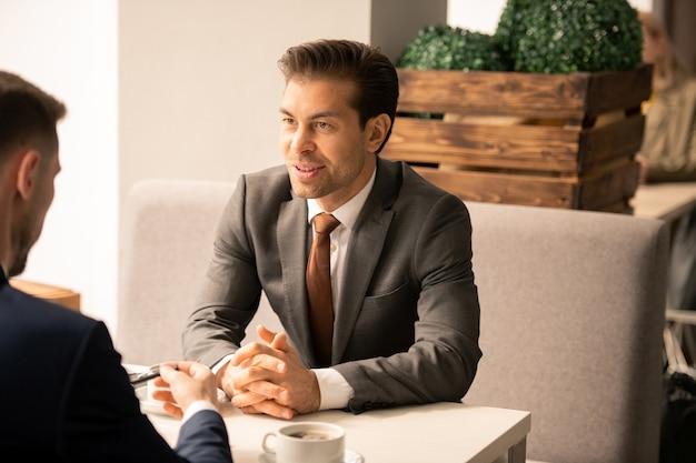 Zwei junge elegante geschäftspartner sitzen am tisch im café voreinander und diskutieren arbeitsfragen