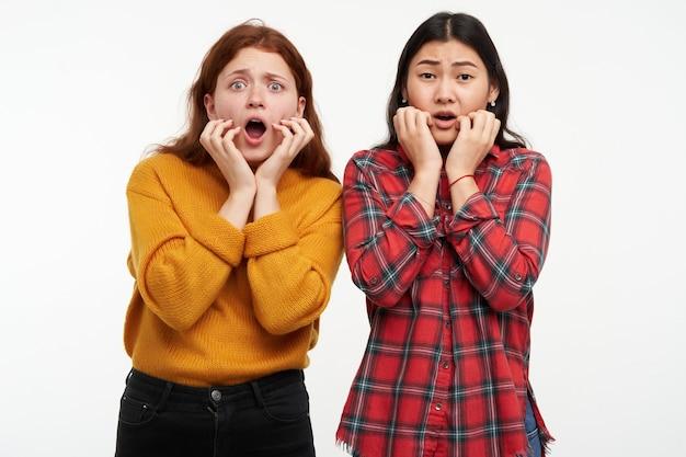 Zwei junge, entsetzte frauen. freunde schauen sich einen horrorfilm an. personenkonzept. gesicht vor angst berühren. tragen eines gelben pullovers und eines karierten hemdes. isoliert über weiße wand