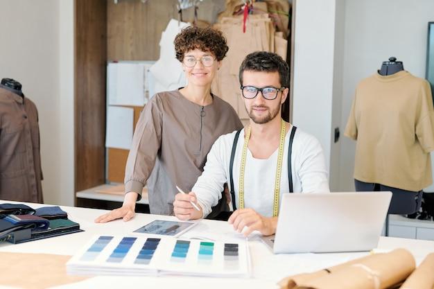 Zwei junge erfolgreiche modedesigner, die mobile geräte verwenden, während sie in der werkstatt an einer neuen saisonalen kollektion arbeiten