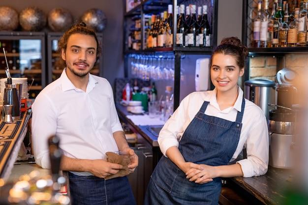 Zwei junge erholsame arbeiter des cafés, die nebeneinander vor der kamera auf hintergrund des regals mit weinsortiment stehen