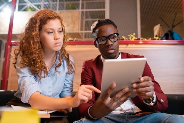 Zwei junge ernsthafte interkulturelle angestellte in der freizeitkleidung diskutieren elektronisches dokument auf touchpad-anzeige beim treffen
