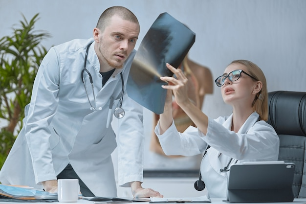 Zwei junge fachärzte besprechen das röntgenbild sorgfältig, das mädchen untersucht es genauer
