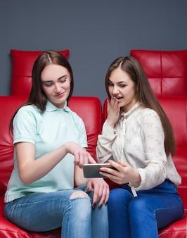 Zwei junge frau, die bilder am telefon betrachtet