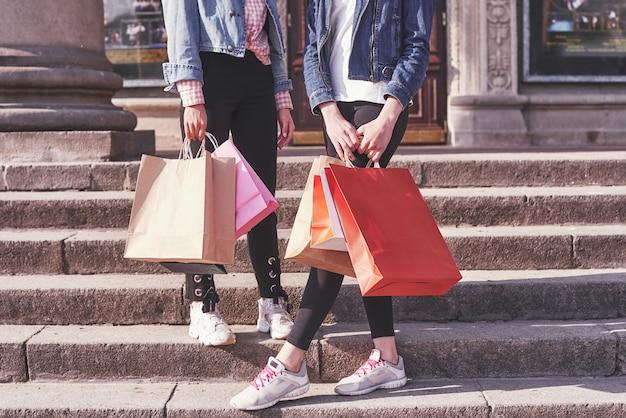 Zwei junge frau, die einkaufstaschen beim gehen auf der treppe nach dem besuch der geschäfte trägt.