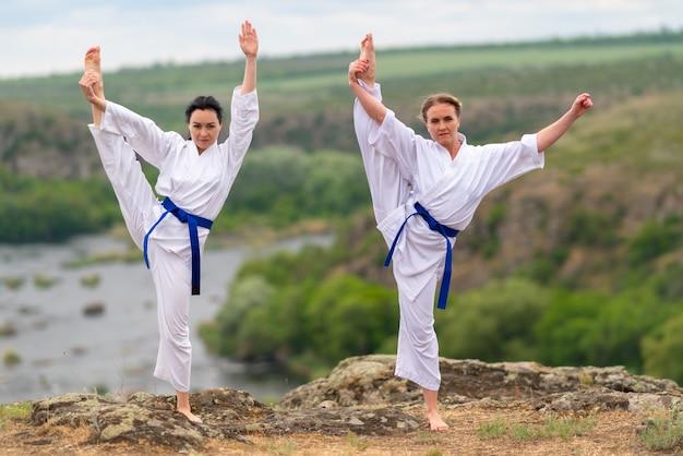 Zwei junge frau, die zusammen acro yoga in einer synchronisierten pose macht