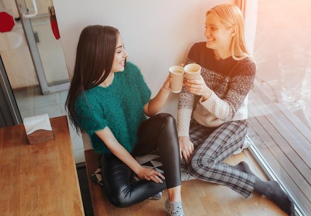 Zwei junge frau im chat in einem café. zwei freunde, die zusammen kaffee genießen