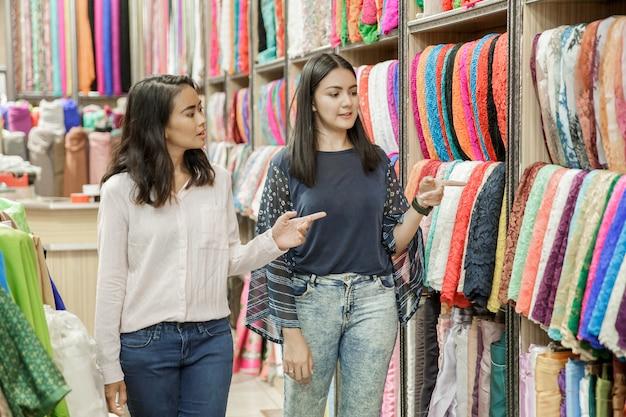 Zwei junge frau shoppic am stoffladen