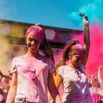 Zwei junge frauen bedeckt mit holi farbtanzen im holi festival