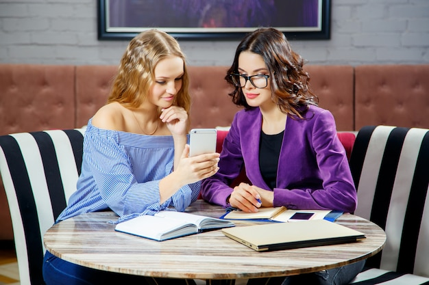 Zwei junge frauen besprechen die geschäftsfragen, die das telefon im restaurant betrachten