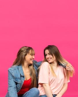 Zwei junge frauen, die an einander lächeln