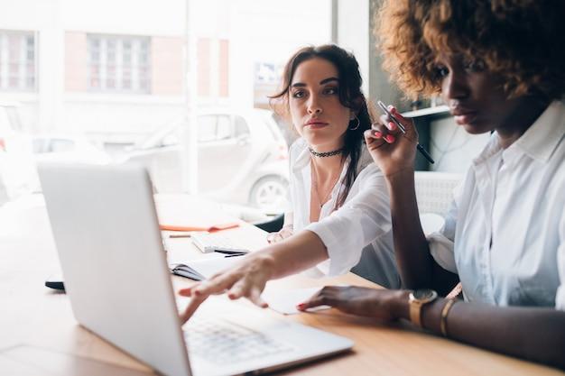 Zwei junge frauen, die an einem projekt mit laptop arbeiten