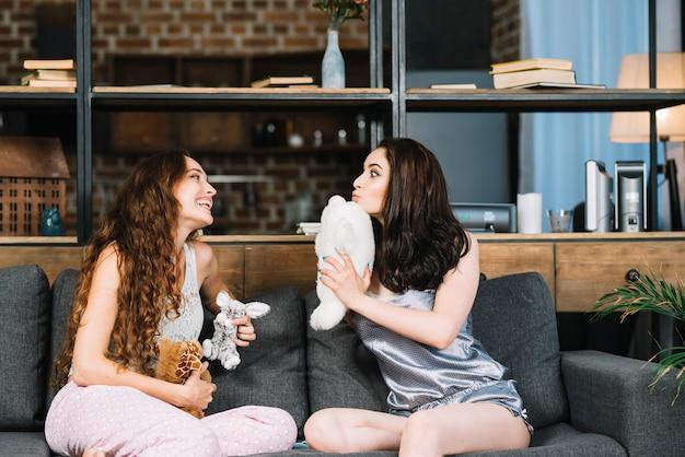 Zwei junge frauen, die auf dem sofa hält weiches spielzeug sitzen