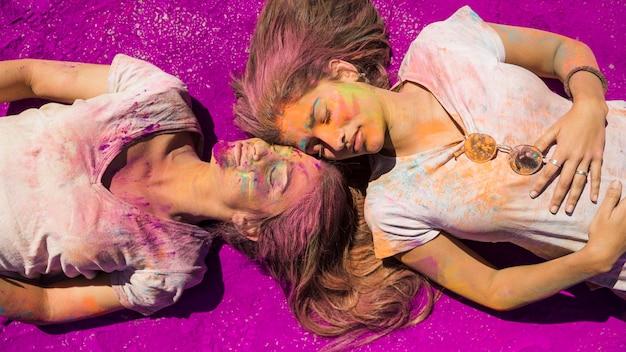 Zwei junge frauen, die auf rosa holi farbpulver liegen