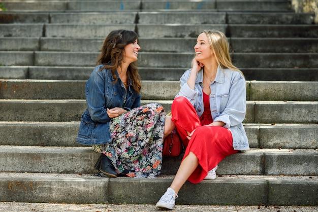 Zwei junge frauen, die auf städtischen schritten sprechen und lachen.