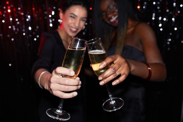 Zwei junge frauen, die champagnergläser anstoßen, während sie auf der party gegen funkelnden hintergrund stehen, konzentrieren sich auf vordergrund