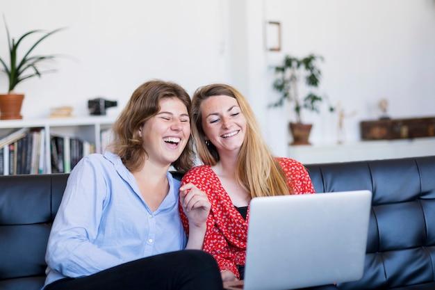 Zwei junge frauen, die computer beim sitzen auf couch im wohnzimmer verwenden