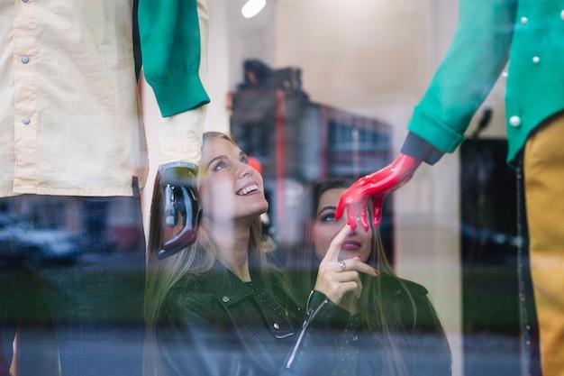 Zwei junge frauen, die das fenstereinkaufen vor butikenspeicherausstellungsfenster tun