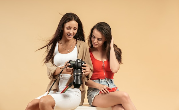 Zwei junge frauen, die fotos auf professioneller kamera auf beigem hintergrund ansehen