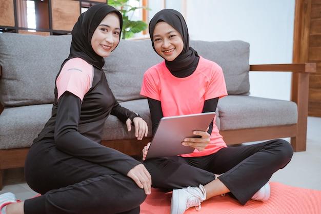 Zwei junge frauen, die hijab-sportkleidung tragen, lächeln, während sie sich auf dem boden entspannen, während sie ein digitales tablet verwenden, das sich zu hause auf das sofa stützt