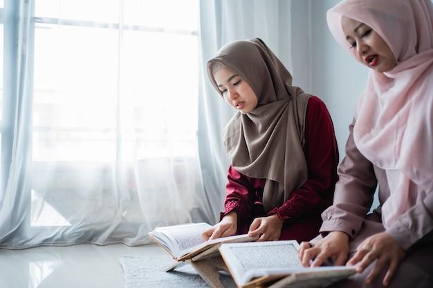 Zwei junge frauen, die hijabs tragen, lesen gemeinsam das heilige buch des al-quran