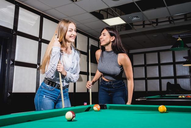 Zwei junge frauen, die im billard spielen.