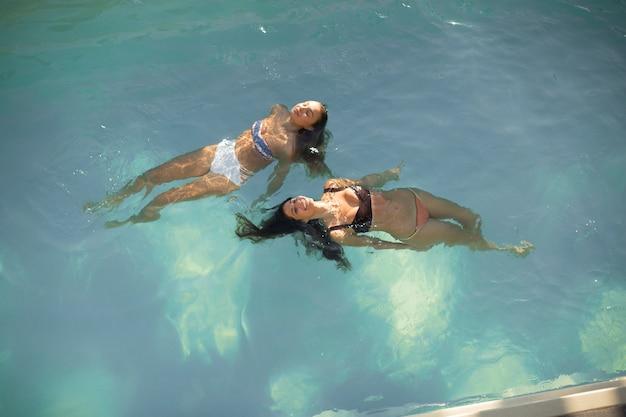 Zwei junge frauen, die in den swimmingpool schwimmen