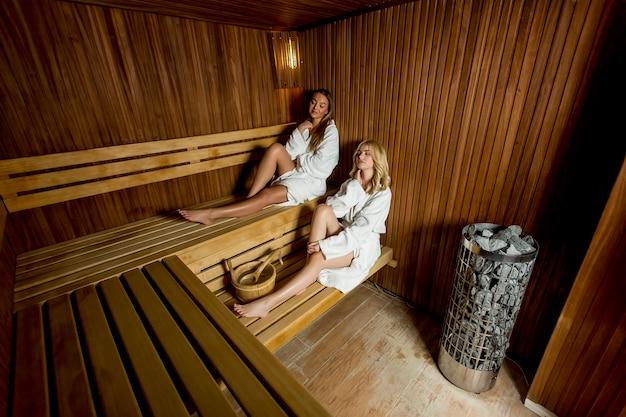 Zwei junge frauen, die in der sauna sich entspannen