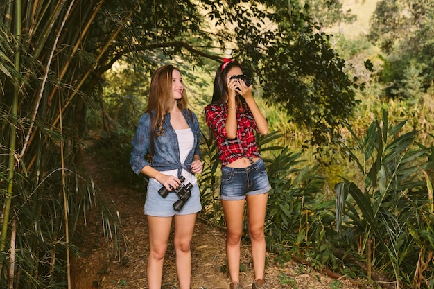 Zwei junge frauen, die in klickender fotografie des waldes mit kamera stehen