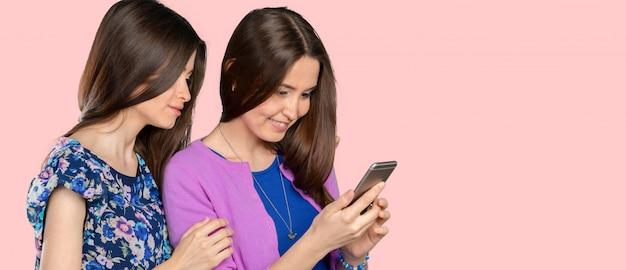 Zwei junge frauen, die intelligentes telefon verwenden