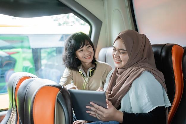 Zwei junge frauen, die lächeln, während sie plaudern und tabletten benutzen, sitzen im bus