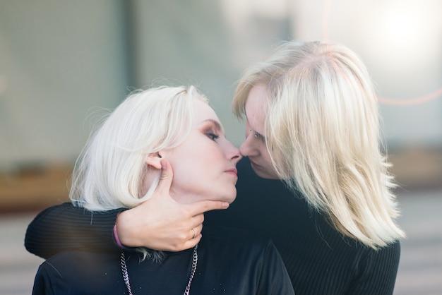 Zwei junge frauen, die lächelnd im freien in der stadt umarmen und küssen gehen