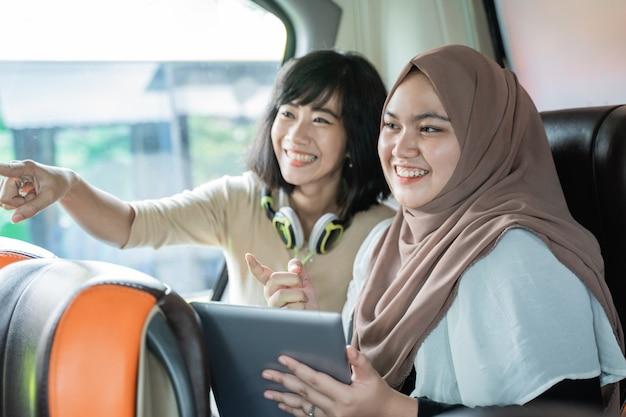 Zwei junge frauen, die mit zeigenden fingern lächeln, während sie plaudern, während sie eine tablette halten, die auf dem bus sitzt