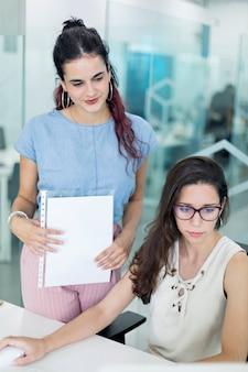 Zwei junge frauen, die mitteilungen auf bildschirm, in einem coworkingraum aufpassen