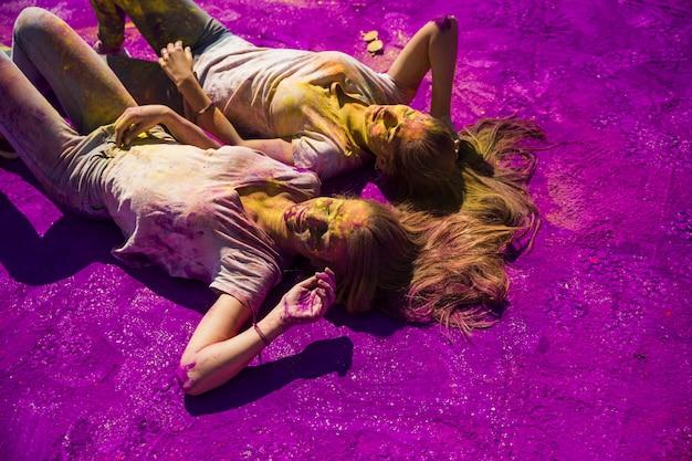 Zwei junge frauen, die nebeneinander auf purpurrotem holi pulver liegen