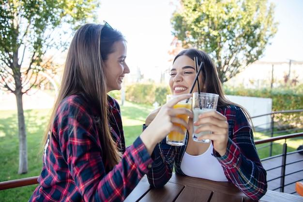 Zwei junge frauen, die saft und limonade im park trinken