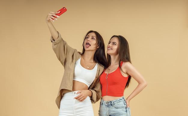 Zwei junge frauen, die selfie auf smartphone auf lokalisiertem beigem hintergrund nehmen