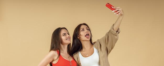 Zwei junge frauen, die selfie auf smartphone nehmen und zunge heraus auf beigem hintergrund heraushalten