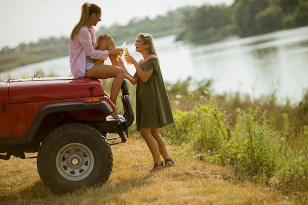 Zwei junge frauen, die spaß auf haube eines roten autos haben