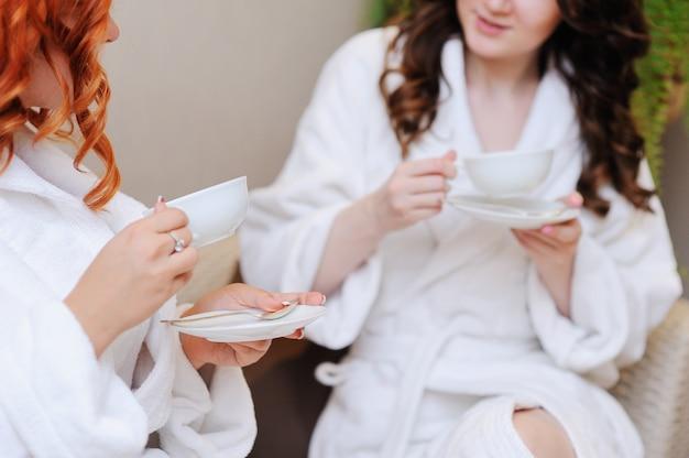 Zwei junge frauen, die tee nach badekuren trinken