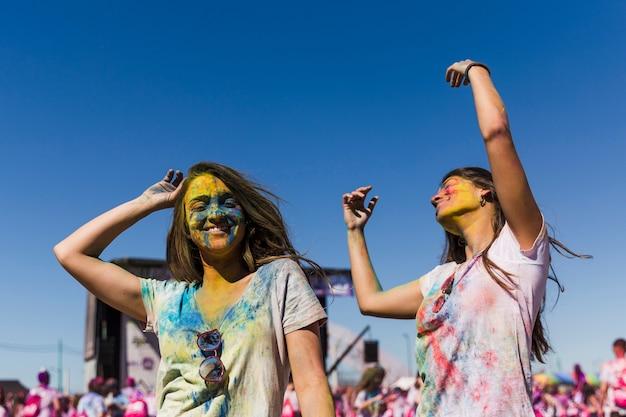 Zwei junge frauen, die während des holi festivals tanzen