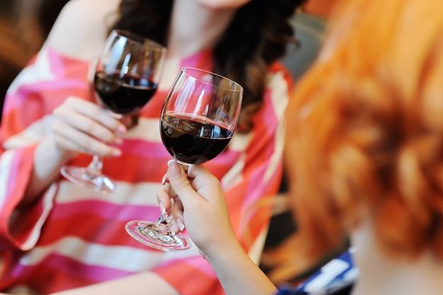 Zwei junge frauen, die wein in einem restaurant trinken. weinprobe