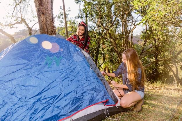 Zwei junge frauen, die zelt für das kampieren einstellen