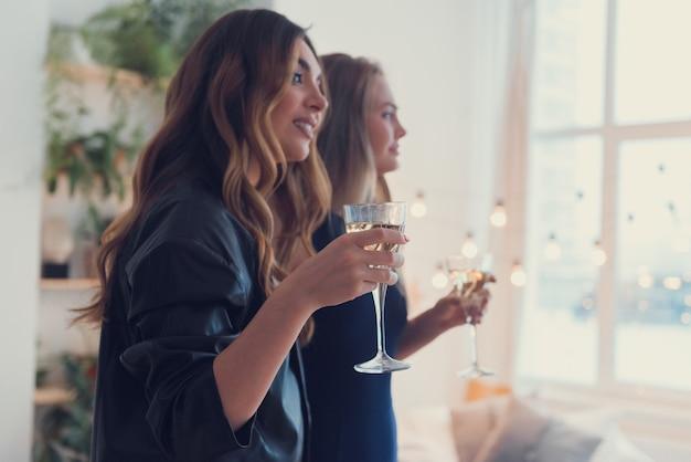 Zwei junge frauen feiern drinnen mit weingläsern neujahr oder geburtstag