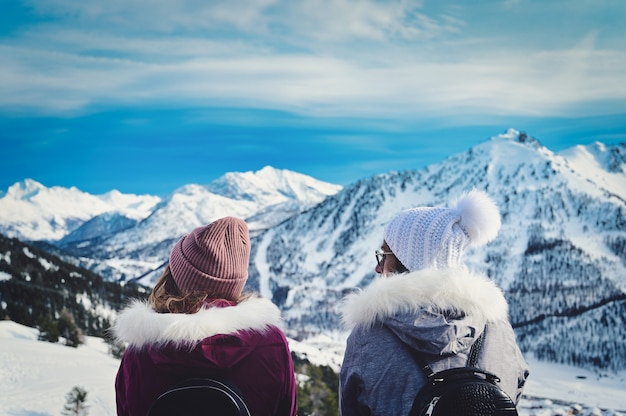 Zwei junge frauen genießen die aussicht auf die schneebedeckten berge