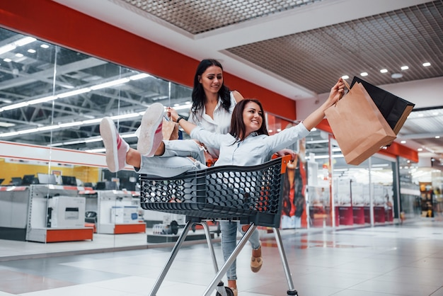 Zwei junge frauen haben spaß beim laufen und reiten im einkaufskorb im supermarkt.