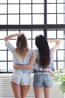 Zwei junge frauen hängen zusammen rum