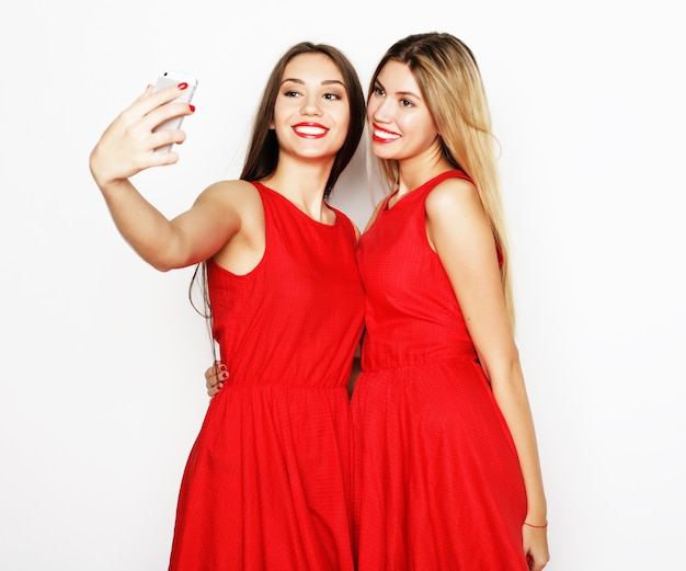 Zwei junge frauen im roten kleid, die selfie mit dem handy machen mobile